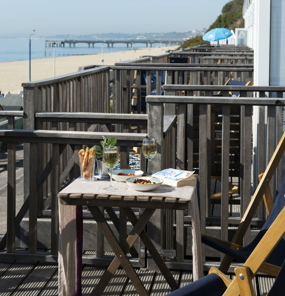 An outside shot of the Beach Lodges on a bright and warm day, featuring two deck chairs with a table featuring small dishes of olives and strawberries, bread sticks and two glasses of wine