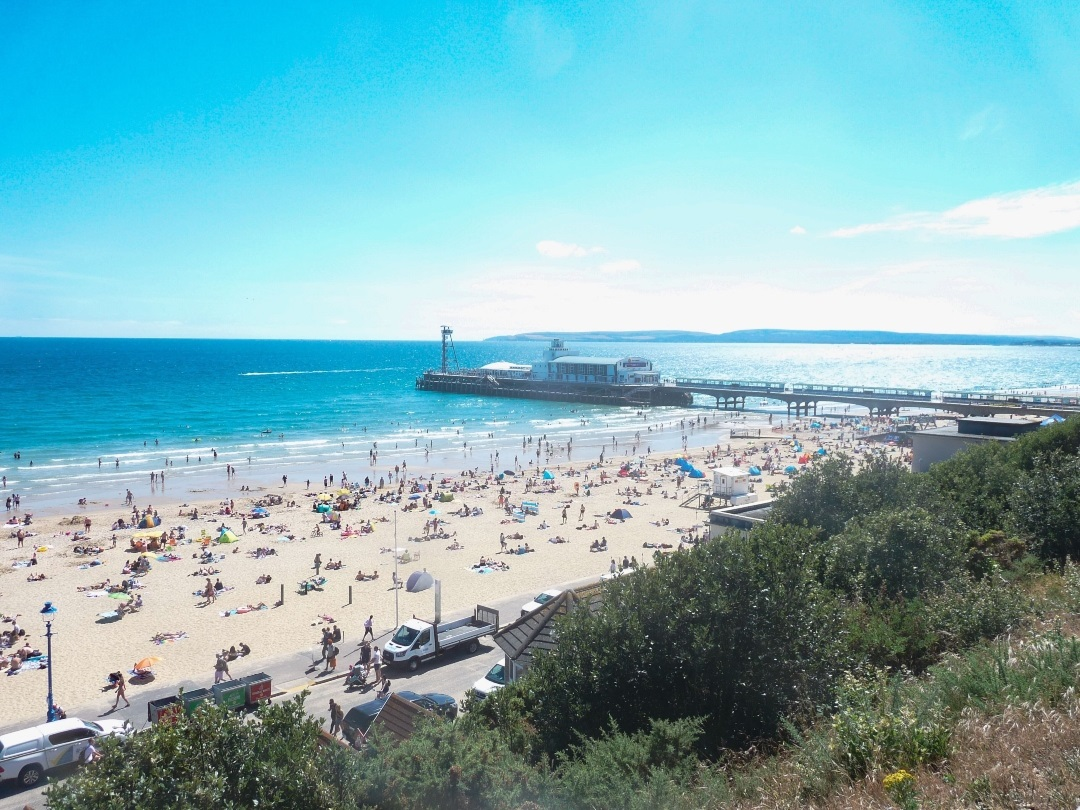 A relatively busy Bournemouth Beach under clear blue skies looking towards the Pier in the near-distance