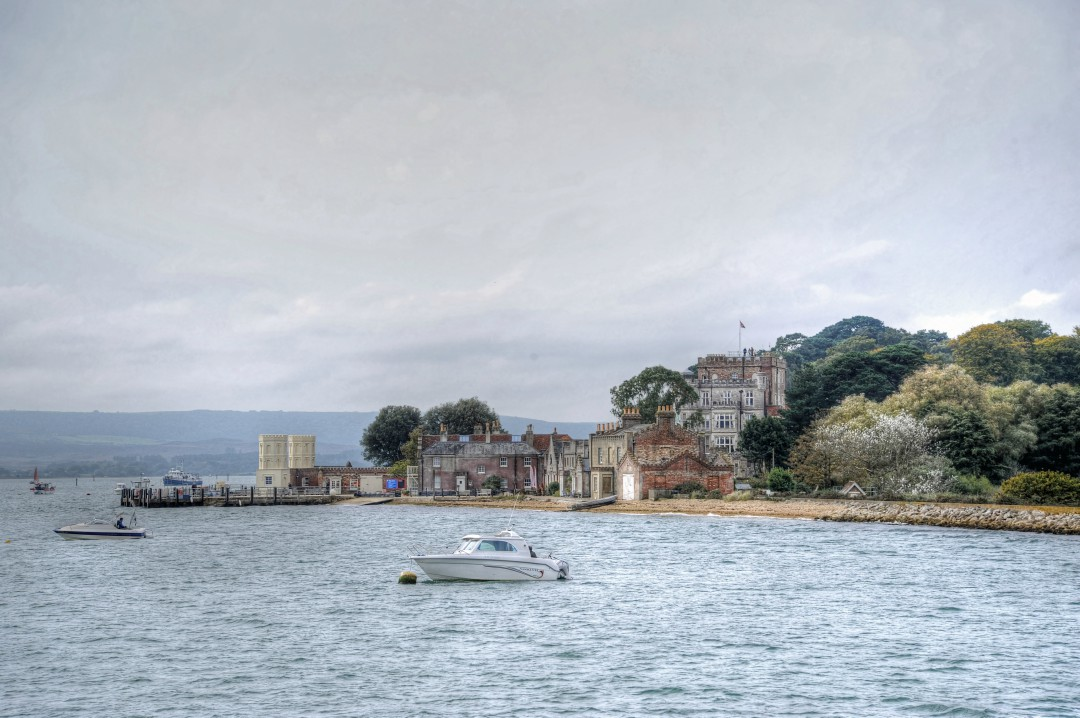 A view across the harbour towards Poole's iconic Brownsea Island, with boats dotted along the waterline. A prominent building composed of traditional red and grey brick sits in the background