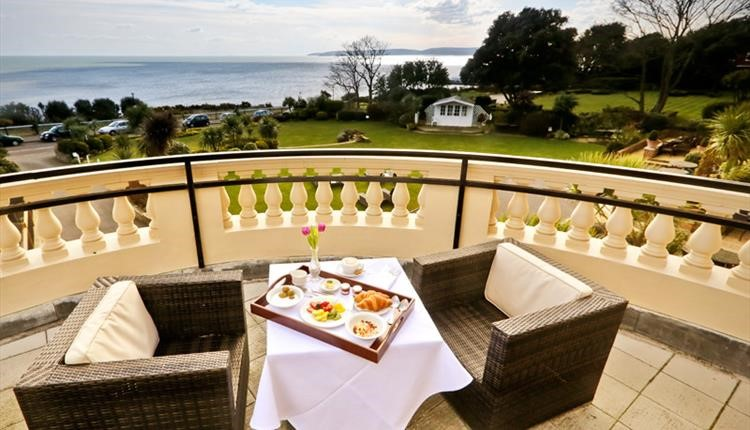 Continental breakfast laid up on table with views overlooking the garden and sea