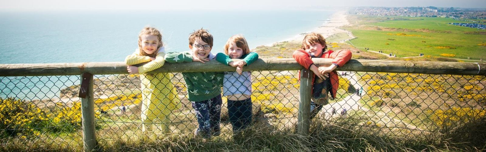 Kids posing for photo on a fence with the seaside behind them