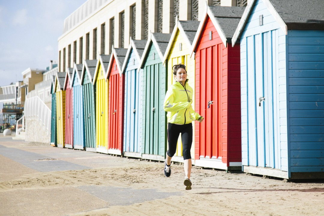 A woman in a high-vis yellow jacket running alongside a sunny Bournemouth seafront