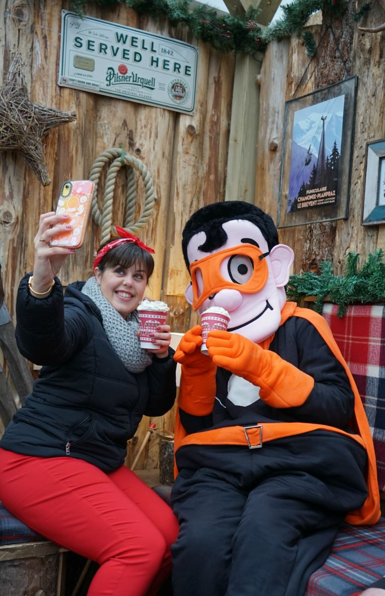 At Bournemouth's SKATE ice-rink, a young woman takes a selfie with a super-hero mascot dressed in black with an orange cape