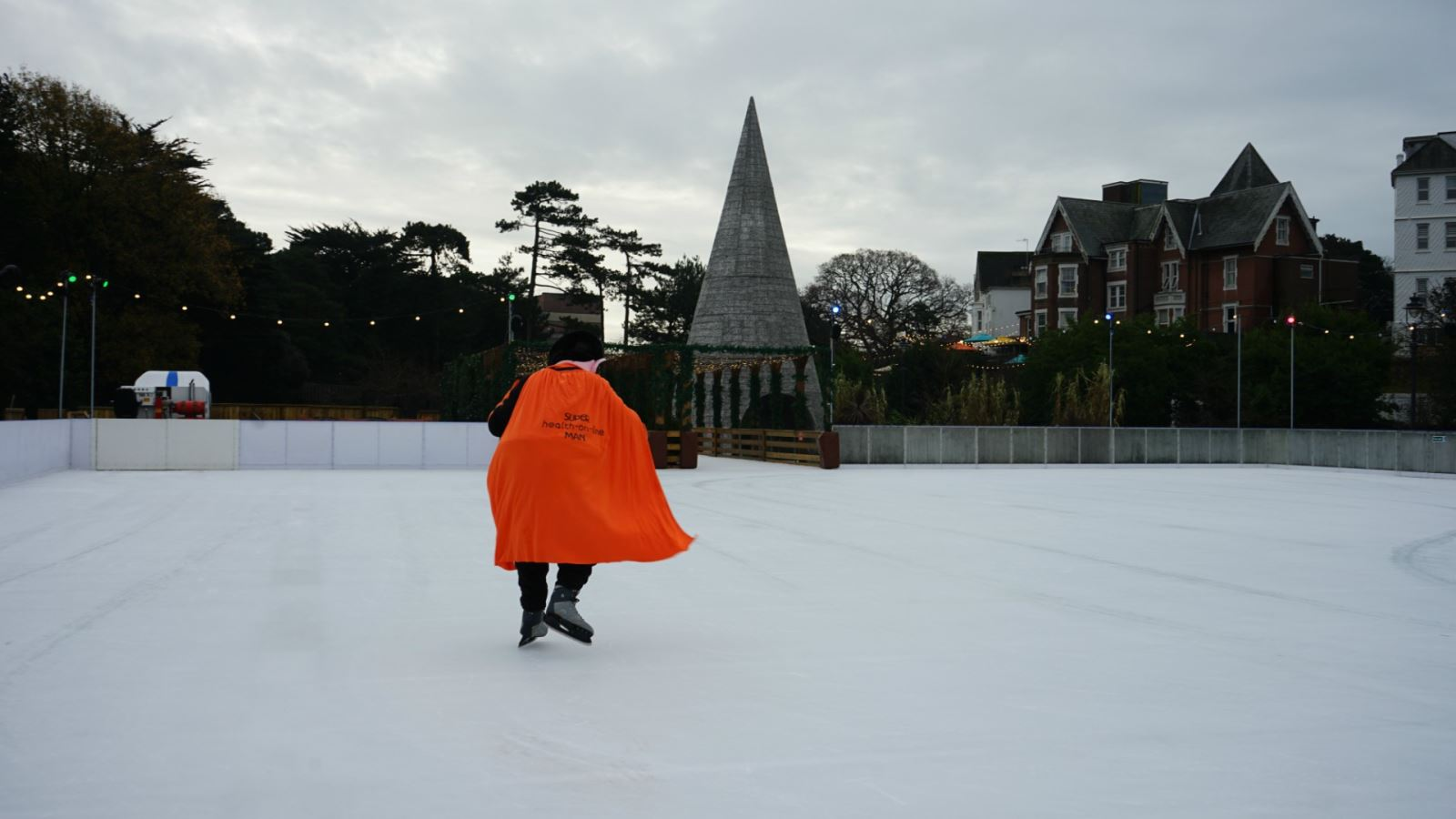 Mr Health on Line in Bournemouth, ice-skating away as his orange cape is blown by the wind