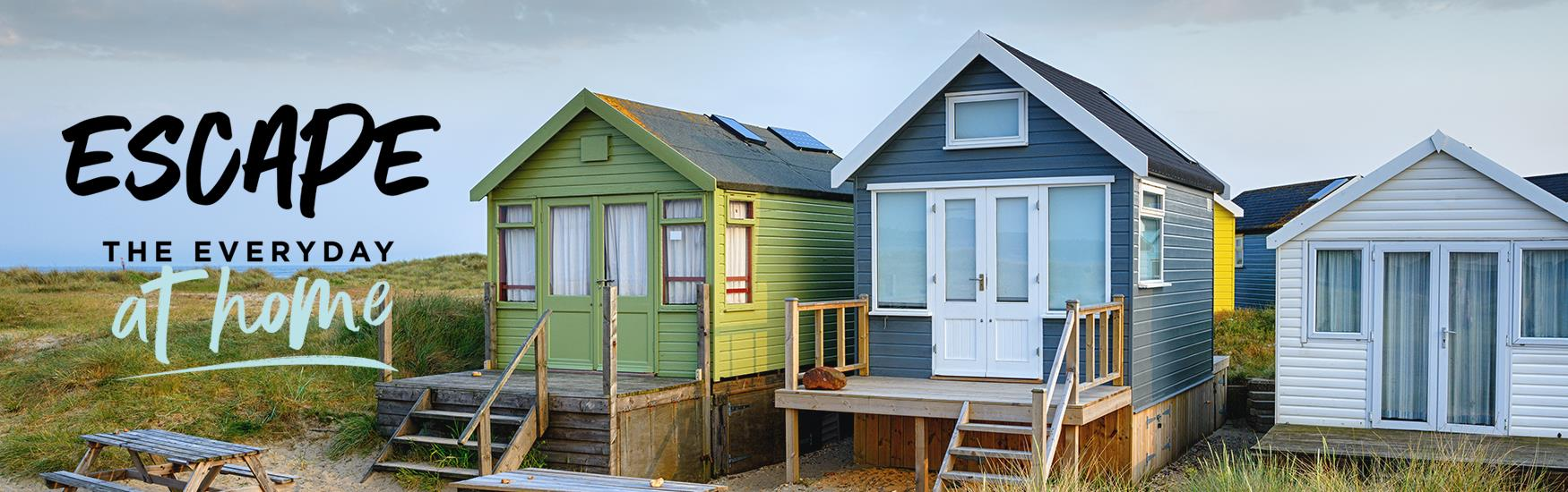 Mudeford Beach huts in the day with the text Escape the Everyday at home