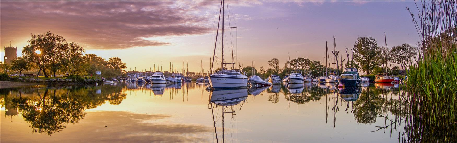Sunset image of boats on Christchurch quay with the priory church in the distance