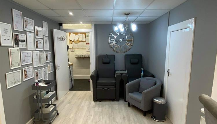 Grey interior with bright white lighting and a fashionable clock on the wall.
