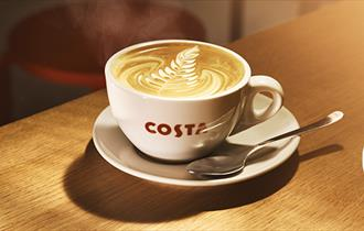 cup of costa coffee on a wooden bench.