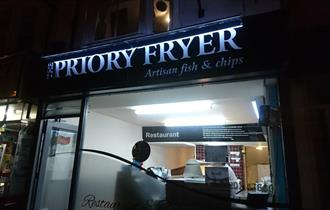 Priory fish and chips lit up at night.