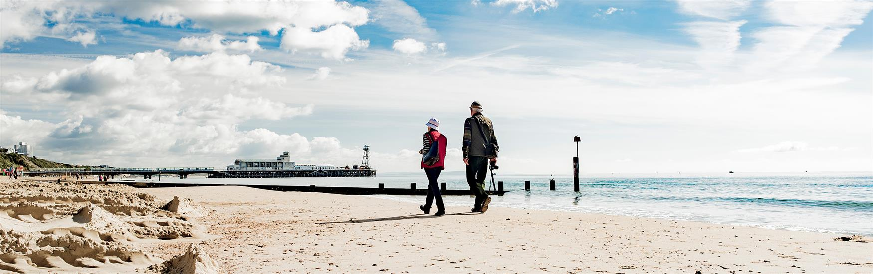 Couple walking towards the pier along Bournemouth beach in the Spring