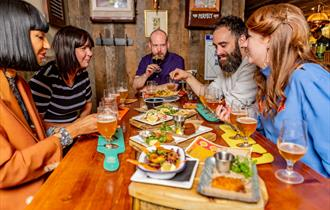 Five people around a table enjoying a selection of food and beer.