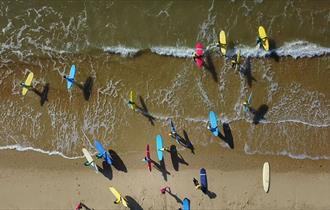 surfers from above in the sea with their brightly coloured boards
