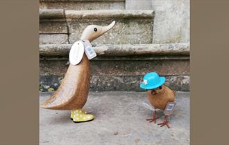 Two wooden ducks on a stone step