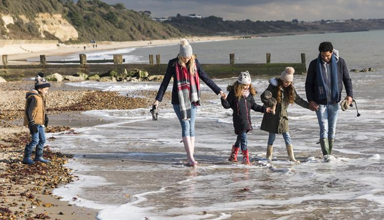 Family wrapped up warm whilst dipping their feet in the sea