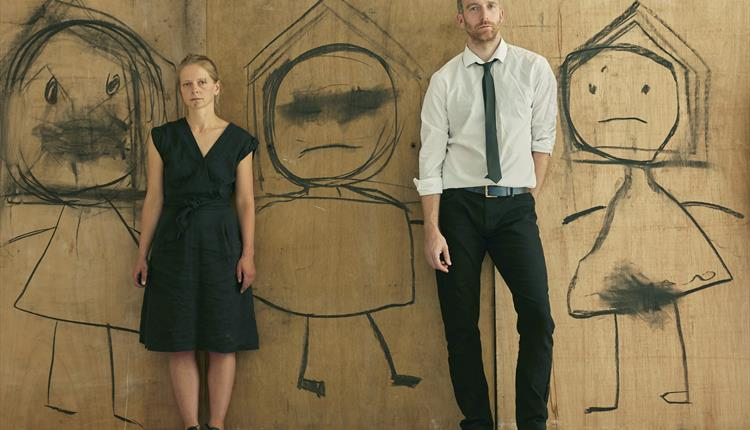 A man and woman standing against a wooden wall