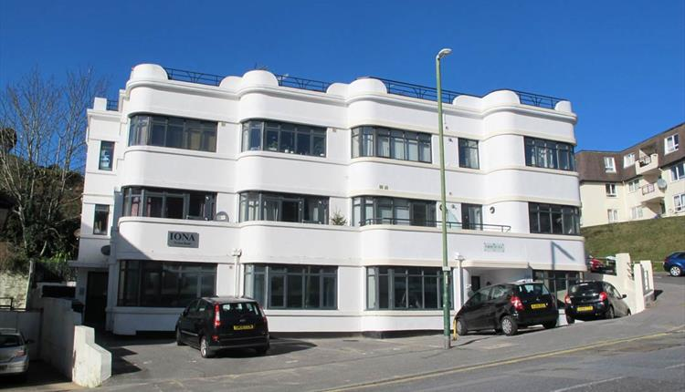 Exterior shot of the white Iona Holiday flats building from the road