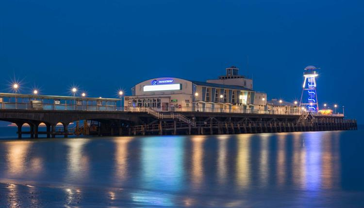 Bournemouth pier illuminating the still night sky