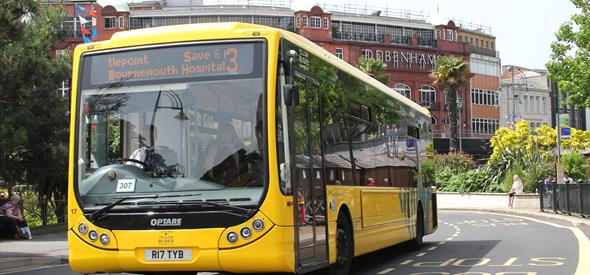 Yellow bus through centre of Bournemouth, Debenhams in the background