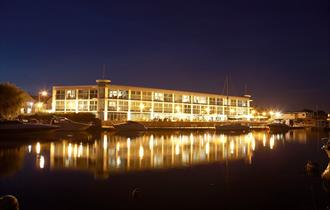 Waterside exterior of the Christchurch hotel lit up at night.